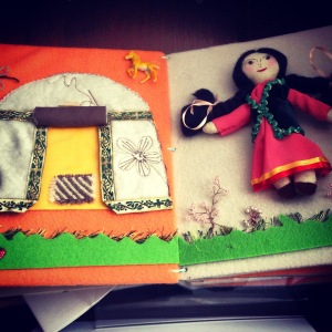 A book page made of felt, ribbon, embroidery, and other fabric. The page on the left is a representation of a yurt. There is a rug, a horse, and grass. A yurt is a canvas tent-like dwelling that can be moved.