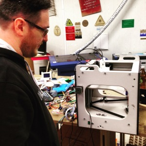 A man standing beside a small personal scale 3D printer, sitting on a desk with a lot of wires and other crafting tools.