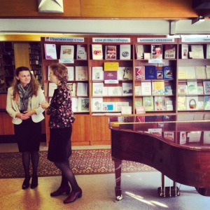 Two woman standing in front of a book shelf talking.