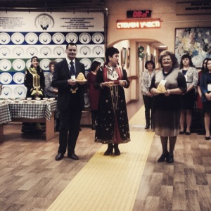 Three people standing in the entrance of a room, holding gifts as symbols of their greetings. The Director of the library is dressed in a traditional Bashkir gown.