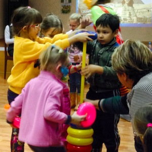 Four kids putting round objects on a stick, an activity that is symbolic of building.
